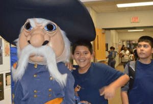 Sixth-grader David Arellano poses with Godfrey-Lee Rebel mascot
