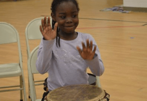 Second-grader Jalyhia Reid bangs on the drum