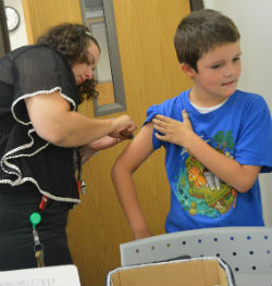 Sara Cinadr gives third-grader Jayden Mast an insulin shot