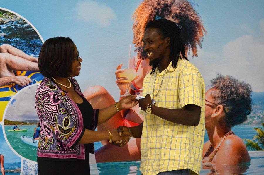 Mrs.-Arlene-Buckmire-Outram,-PS-of-Ministry-of-Tourism-hands-a-certificate-to-a-Grand-Anse-beach-salesperson