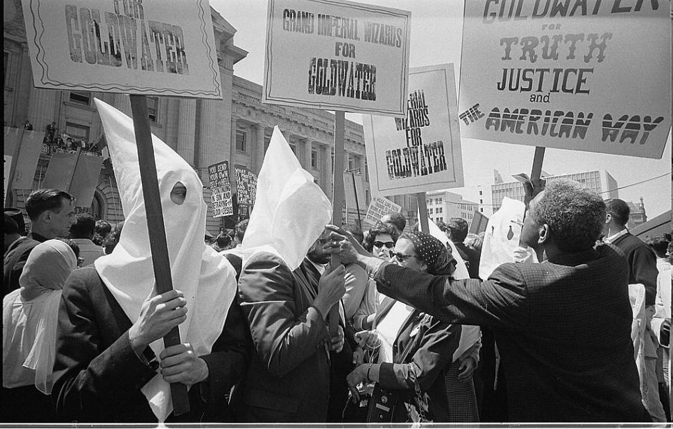 Ku Klux Klan members supporting Barry Goldwater's campaign for the presidential nomination at the Republican National Convention, San Francisco, California, as an African American man pushes signs back.