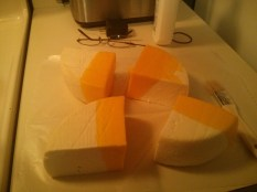 Dip cheese into melted wax then put on wax paper to dry. Repeat until entire cheese is waxed, using the paintbrush to seal in any gaps.