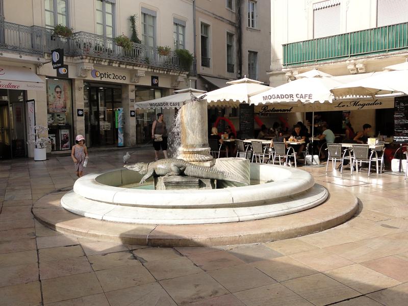 La Place du Marché et sa fontaine au crocodile. Le crocodile est l'emblème de Nîmes, on le trouve un peu partout, ouvrez l'oeil!