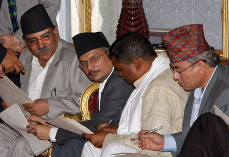 """On 18 August 2008 Pushpa Kamal Dahal """"Prachanda"""", left, was sworn in as Prime Minister. He looks on as Finance Minister Baburam Bhattarai, second left, Foreign Minister Upendra Yadav, second right, and Defence Minister Ram Bahadur Thapa, right, check their papers before being sworn into the cabinet. AP PHOTO/BINOD JOSHI"""