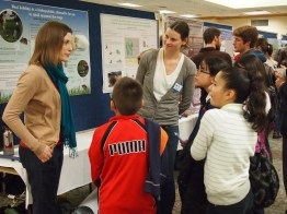 Elementary students investigating posters with GDPE graduate student Whitney Mowll.