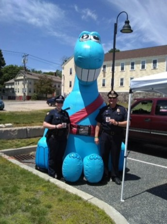 Buckleupallofus Balloon reminds kids and families to Boost Up!, Buckle Up! and use properly installed car seats. Burrillville Police Department Major Dennis Leahey and Officer Jen hold up Bucky fridge magnets.