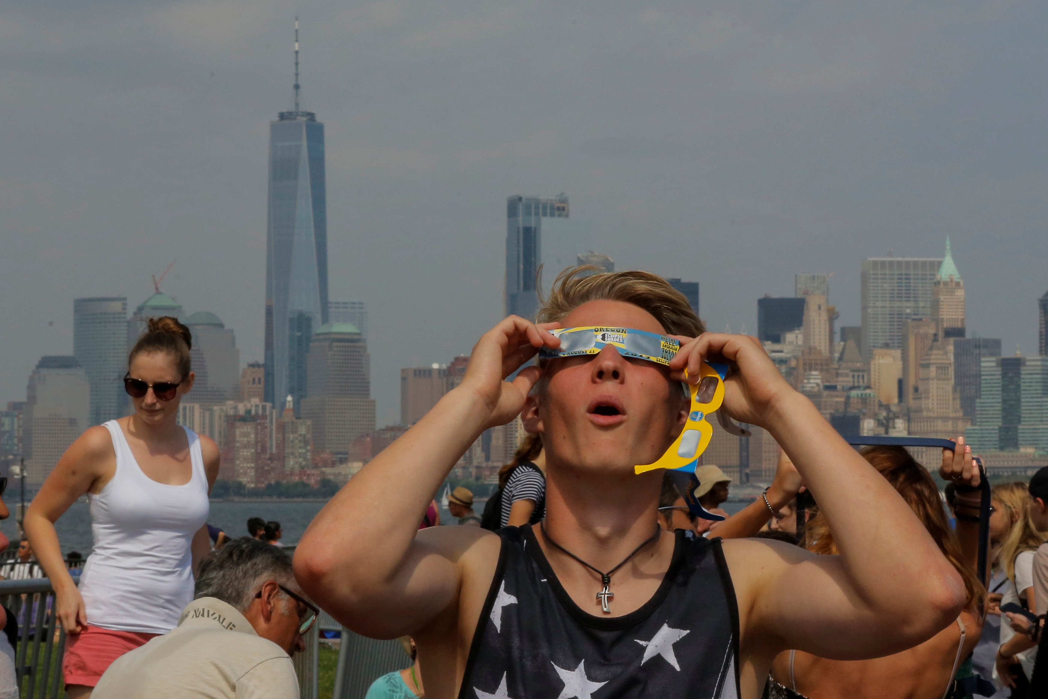 A man takes a look at the solar eclipse at Liberty State Island as the Lower Manhattan and One World Trade center are seen in the background in New York, U.S., August 21, 2017. Location coordinates for this image are 40.4124' N, 74.237'. W
