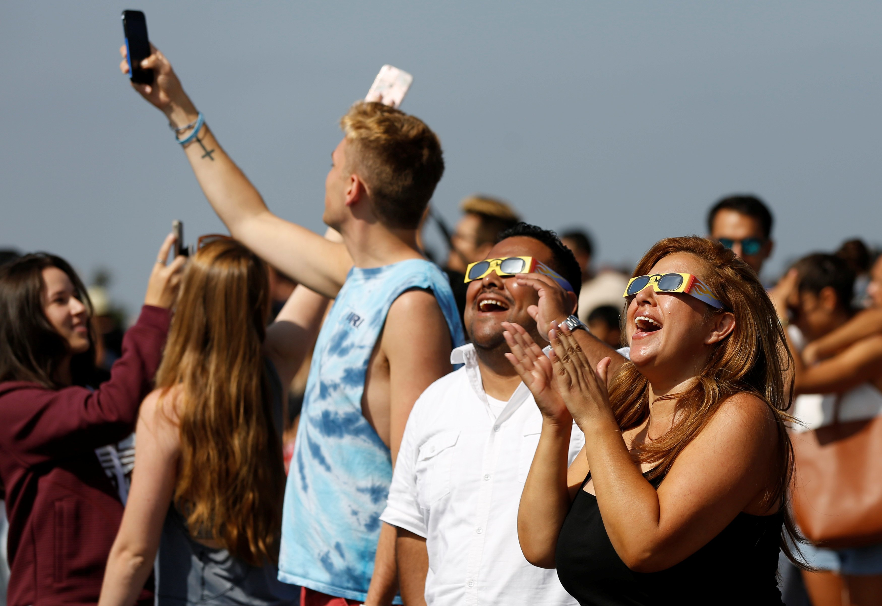 People watch the solar eclipse on the lawn of Griffith Observatory in Los Angeles