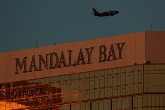 A departing passenger plane flies over the Mandalay Bay hotel in Las Vegas, Nevada, U.S., October 3, 2017. REUTERS/Mike Blake