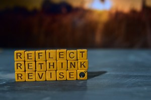 "Wooden letter blocks spelling out the words ""Reflect, revise, rethink"""