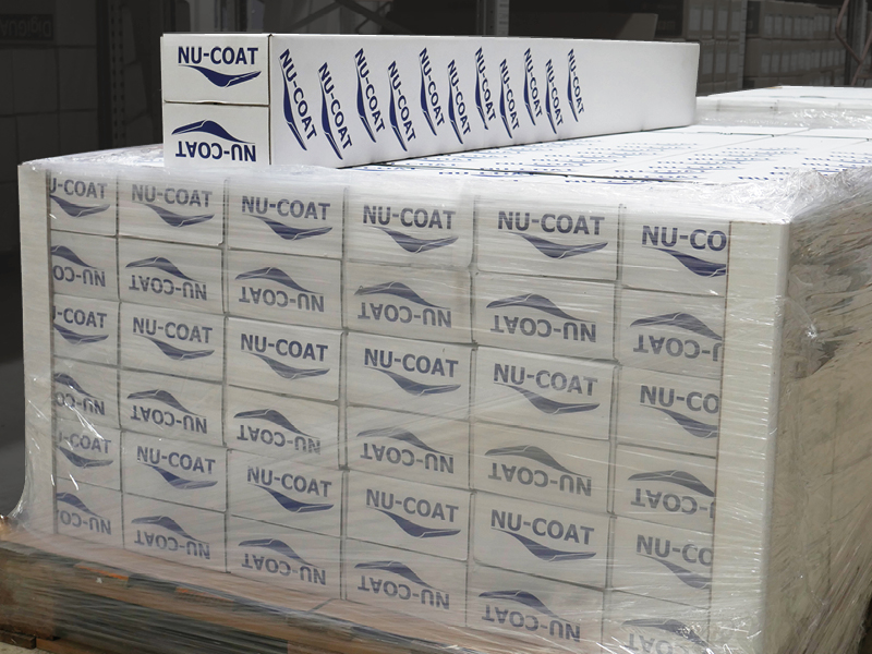 Nu-Coat branded box packaging neatly stacked on a pallet in the warehouse with corner protectors and cling film for added protection of the media rolls.