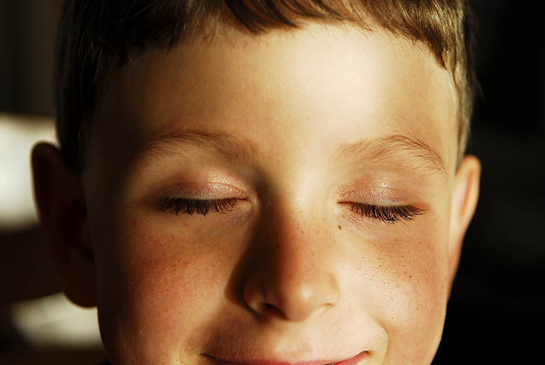 Boy, 6 years old, with his eyes closed showing his long eyelashes. He is looking very content, happy and healthy.