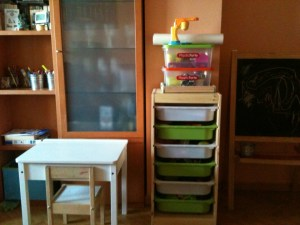 Una mesa y una silla a la altura del niño y un pequeño mueble para guardar sus cositas de artista