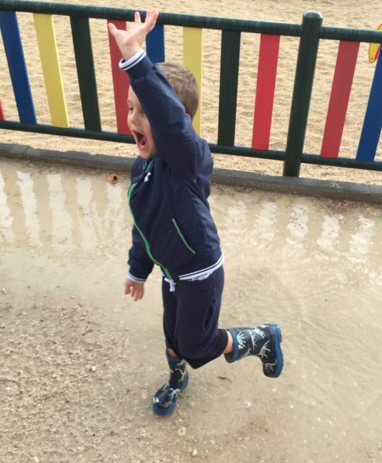 niño saltando charco