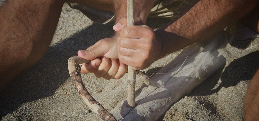 hombre haciendo fuego con palos