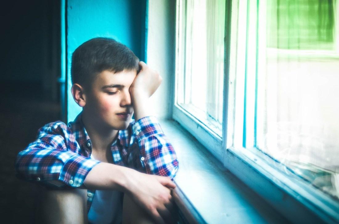 chico triste a la ventana