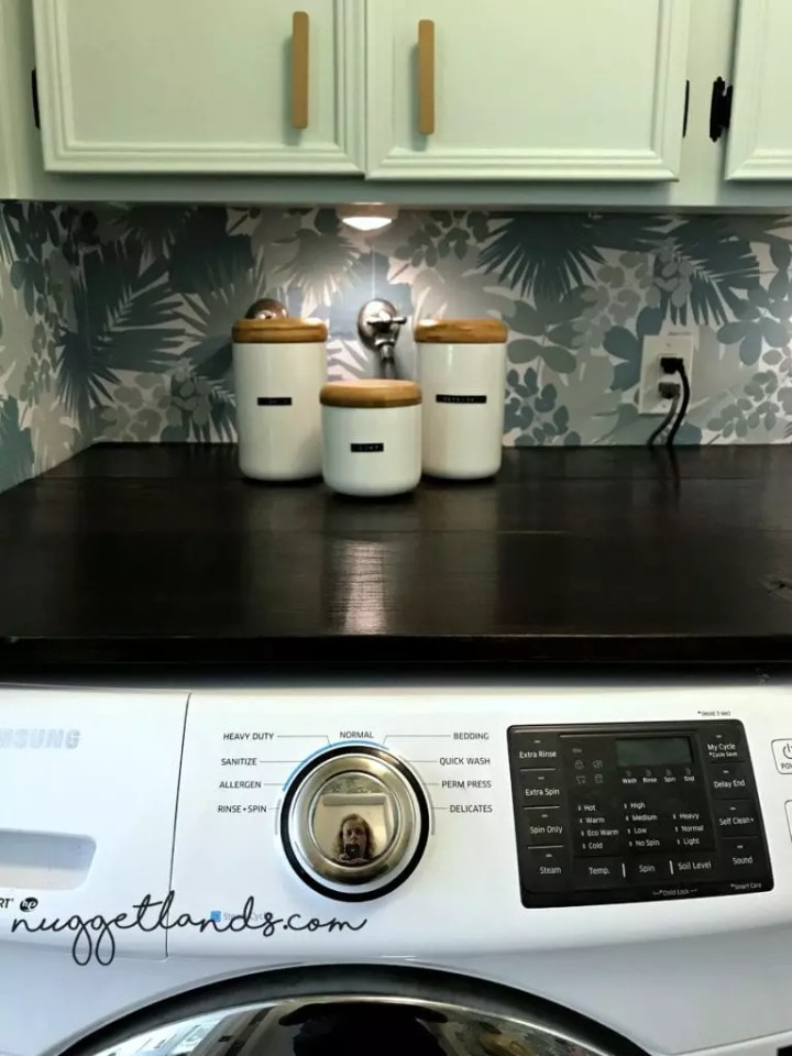 Laundry room shelf for over the washer and dryer that makes a huge impact. An easy DIY project that creates storage and folding space. This stained wood shelf is perfect for small spaces. See our full laundry room makeover for more ideas.