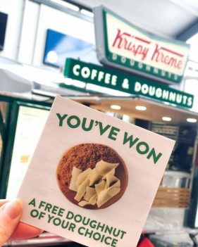 McArthurGlen Bridgend Krispy Kreme with flyer saying 'You've Won a free doughnut of your choice' infant