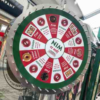 A photo of a Spin To Win board, where you can win free single doughnuts or a box of a dozen