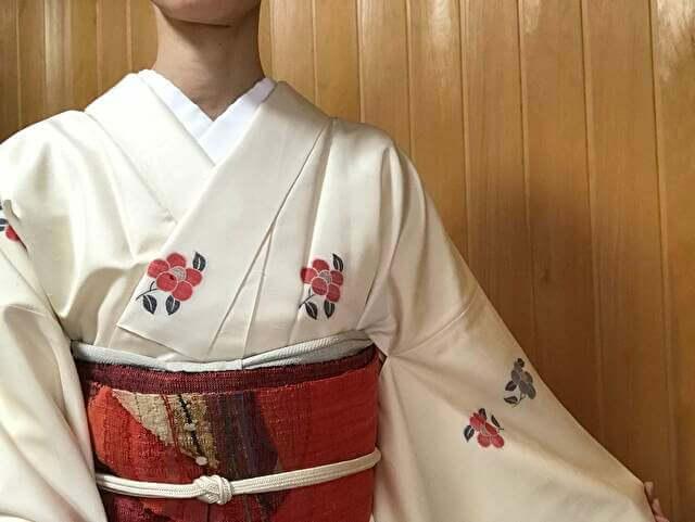 椿文様の白地の紬小紋と渡文の名古屋帯のコーディネート