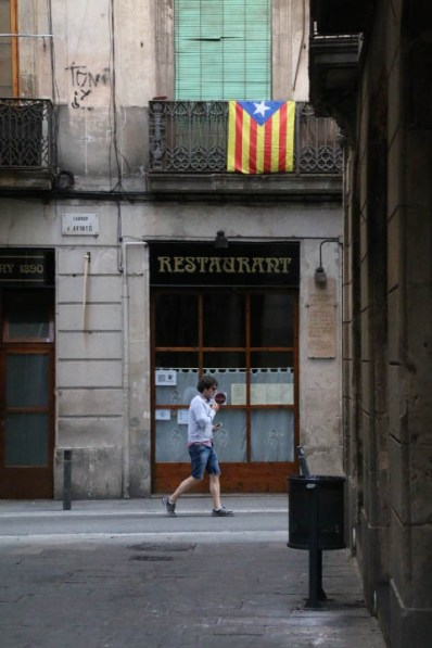 A man passes by an Estelada flag hanging over a restaurant in the Gothic Quarter in Barcelona.