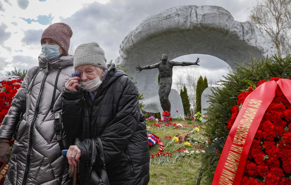 Women mourn near a tomb of a victim of the Chernobyl nuclear power plant disaster at the Mitino cemetery in Moscow...