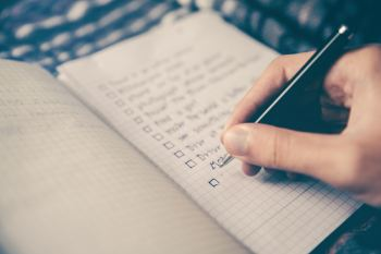 A person writing out a moving checklist in a notebook.
