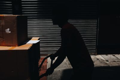 A silhouette of a mover pushing a cart with moving boxes.