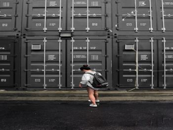 A woman standing in front of grey storage containers.