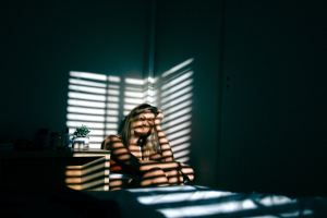 A white woman slumped over with a hand over her head. The light falls on her through the blinds of her windows. The atmosphere is tired and lonely. Is this a picture of expat problems?