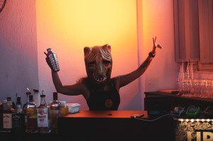 A girl behind the bar wearing a mask of a cat or a bear