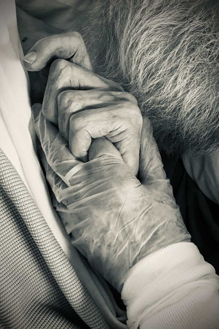 My father's hand holding my sister's finger