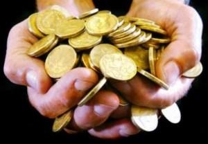 duas mãos juntas cheias de moedas douradas