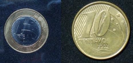 A esquerda uma moeda de um real e a direita uma moeda de 10 centavos, as duas moedas apresentam desgaste no desenho, tendo assim partes não visíveis.
