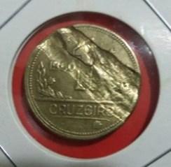 Moeda brasileira onde claramente o disco de metal ao qual a moeda foi batido estava danificado ou quebrado e por isso a fortes marcas transversais de desgaste na moeda
