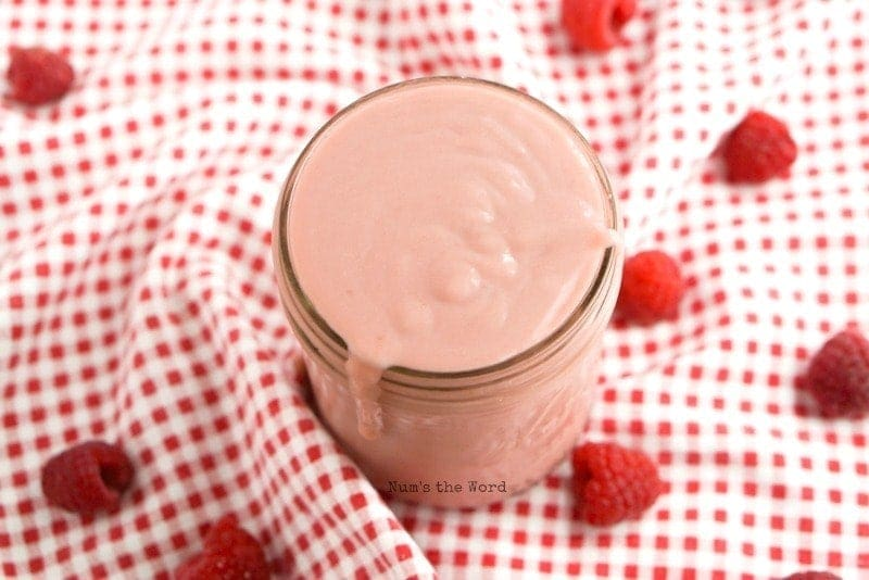 Homemade Raspberry Curd - thickened curd in jar with a drip down the side, down angle