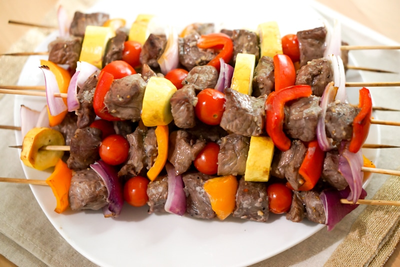 Different angle photo of precooked marinated steak kabobs with vegetables