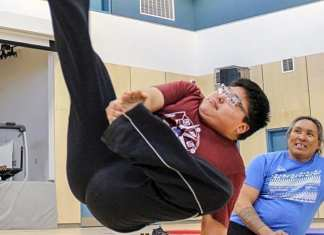 Grade 11 student Lou Kopak tries the Alaskan high kick as motivational speaker and Inuit games athlete Johnny Issaluk, right, offers words of encouragement at Tuugaalik High School in Naujaat on May 2, 2019. Photo courtesy Julia MacPherson