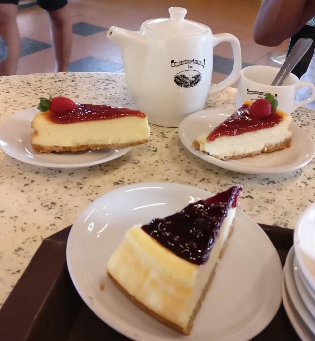 Dos tartas de fresa y una de mora en una mesa con una tetera