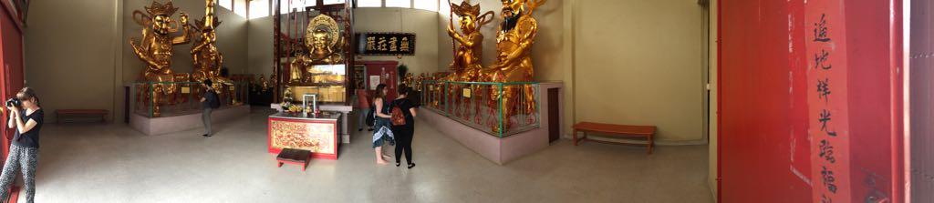 Panorámica del interior del templo, con estatus enormes de dioses budistas de oro. Laura y Nuria observandolas