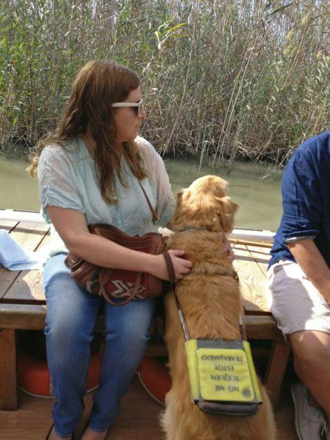 Laura y Grace en la barca por l'albufera. Grace apoya sus patitas en el borde de la barca y mira fijamente el agua
