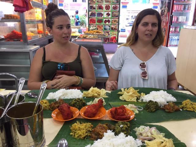 Laura y Nuria en la mesa del restaurante indio. Delante hojas de plátano con arroz pollo rojo y mucha comida