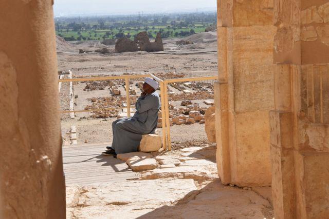 Egipcio sentando en una piedra en el templo de Hatshepsut