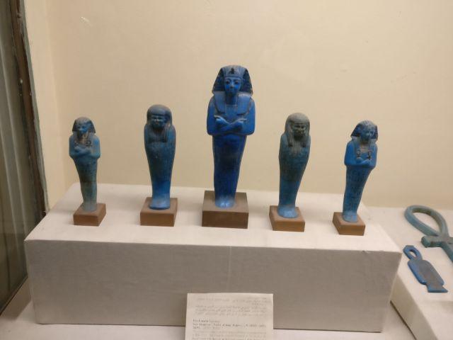 5 figuras egipcias azules que van de mayor a menor, teniendo su figura mas grande en el centro y decreciendo hacia los lados