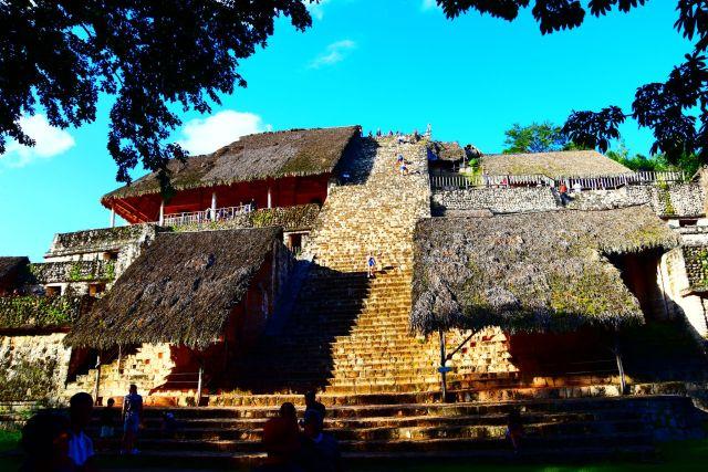 La pirámide desde abajo, se ven todos los escalones ramas de los arboles que la rodean en las esquinas superiores y los edificios construidos a los lados