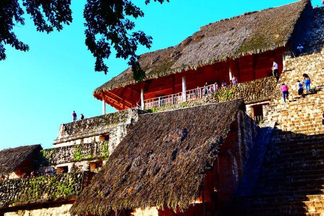 Edificio típico maya, construido pegado a las escaleras de subida, tres plantas todo de piedra con tejado vierteaguas de paja