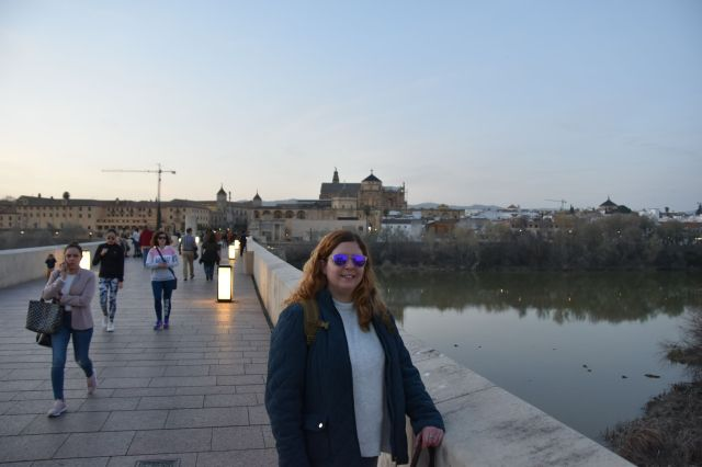 Laura en el puente romano, con la mezquita de fondo. Los faroles del suelo ya están  encendidos, pero aun es de día.