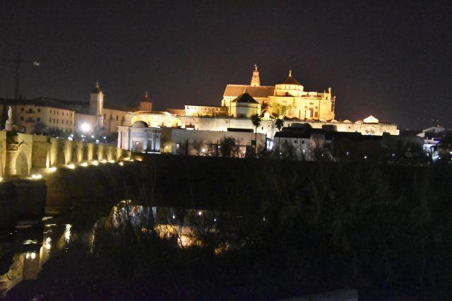 La mezquita de córdoba de noche, iluminada. Se ve parte del puente y se puede apreciar su altura y tamaño