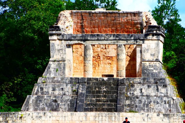 Construcción maya de piedra con una escalinata y en lo alto un techado al que se accede a través de una entrada con columnas