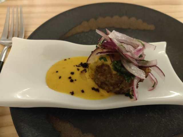 Las bolitas que compartimos, sobre el plato un plato mas pequeño y sobre este una bola depositada sobre la salsa amarilla y con cebolla morada y hierbas por encima de la bola